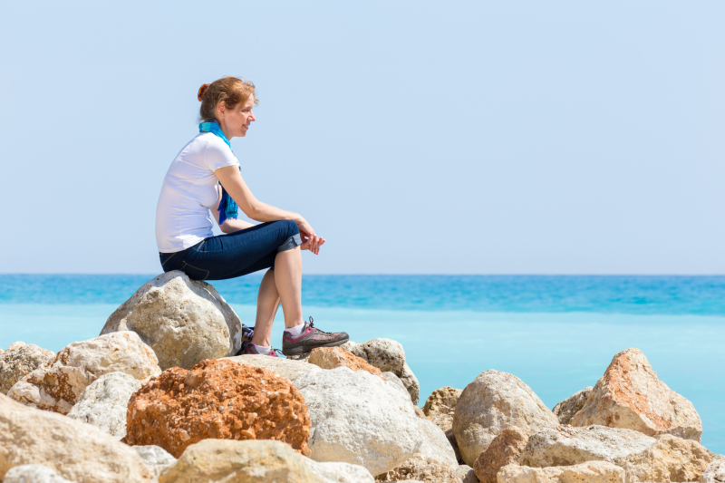 Woman sitting on the rocks at the beach looking out to the water